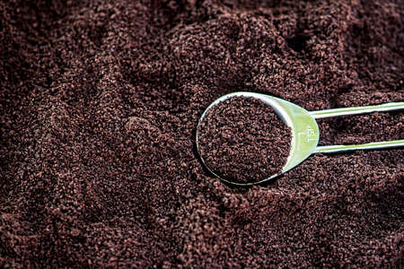 rich flavor: Macro view of coffee ground heap with copper teaspoon, very shallow DOF