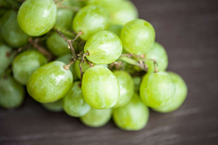 macro: Macro view of a group of juicy, green grapes on a rustic wooden table, shallow DOF
