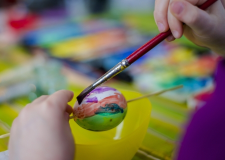 Ostern: a child paints an eastern egg Stock Photo
