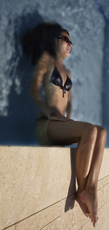 brunette woman in black bikini sitting in water photo