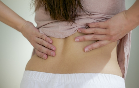 woman back pain: woman has her hand on back due to ache