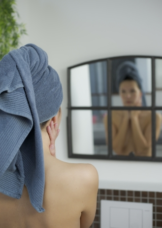woman with a towel on her head looks into mirror photo
