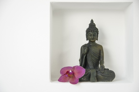 a buddha figure with a violet ordhid blossom in a recession on a white wall photo