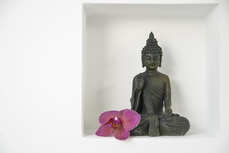 een boeddha figuur met een violette ordhid bloesem in een recessie op een witte muur Stockfoto