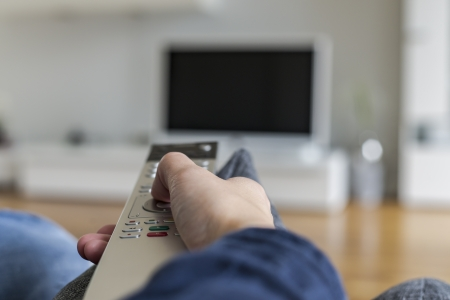 lcd tv: a person with remote control switching channel at home cinema