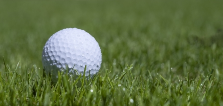 golfball: golfball with waterdrops in grass Stock Photo