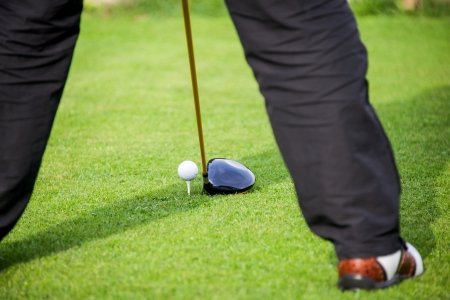 addresses: golfer addresses golf ball with driver in tee box