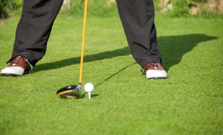 golfer addresses golf ball with driver in tee box