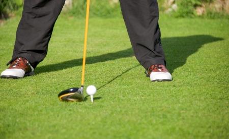 golfer adressen golfbal met chauffeur in tee-box Stockfoto