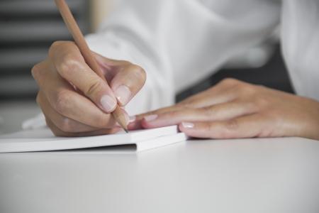 vrouw met potlood schrijft op een vel papier Stockfoto