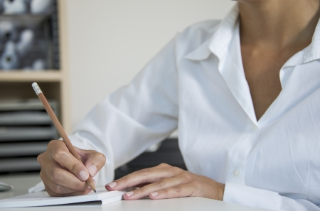 office notes: woman with pencil writes on sheet of paper Stock Photo