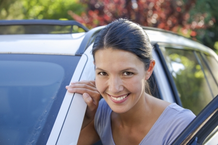 young woman leaning against her car and smiles photo