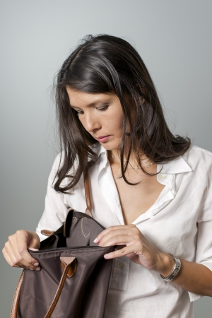 brunette woman searching for purse in handbag