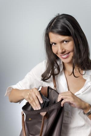 Brunette vrouw op zoek naar portemonnee in handtas Stockfoto