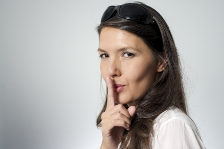 shhh: woman putting her finger to her lips for shhh gesture Stock Photo
