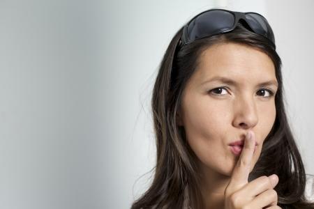 vrouw die haar vinger op haar lippen voor shhh gebaar