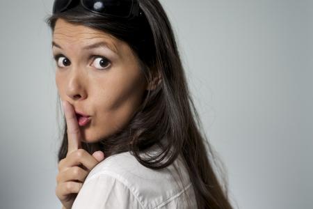 女性 shhh ジェスチャーの彼女の唇を彼女の指を置くこと