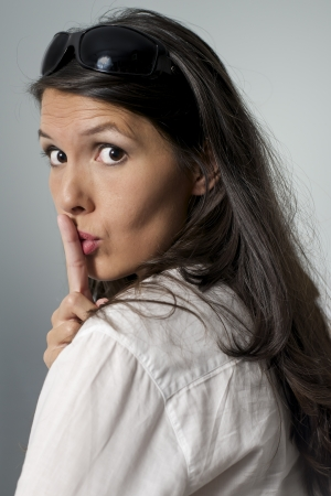 shushing: woman putting her finger to her lips for shhh gesture Stock Photo