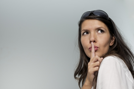 woman putting her finger to her lips for shhh gesture Stock Photo