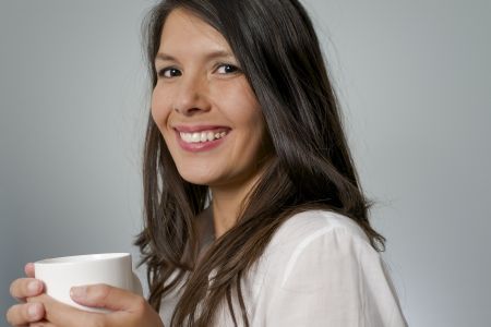 woman drinking coffee out of a white mug photo