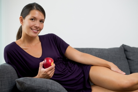 red couch: Pretty young woman holding a fresh crisp red apple in her hand while relaxing on a sofa at home giving the camera a lovely friendly smile Stock Photo