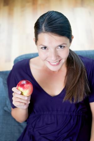 promotes: Vista de �ngulo alto de una hermosa mujer joven que muestra una manzana roja jugosa fresca en la mano mientras se promueve una dieta org�nica sana Foto de archivo