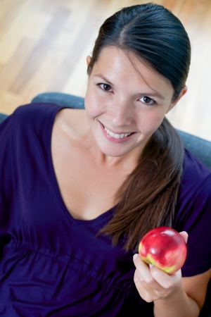 promotes: High angle view of a beautiful smiling young woman showing a fresh juicy red apple in her hand as she promotes a healthy organic diet
