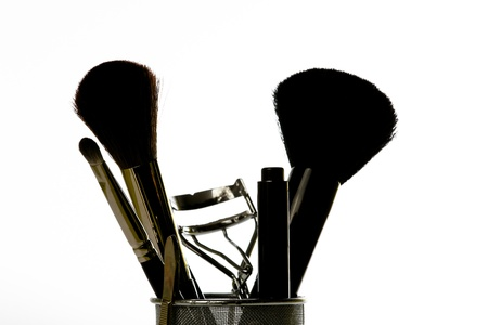 emphasise: Close-up silhouette of some feminine make-up and grooming tools and brushes.