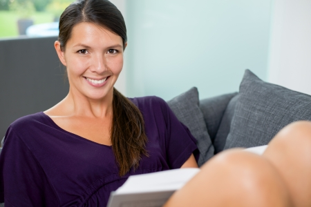 contented: Smiling beautiful young woman relaxing indoors in her living room on a sofa reading a book, close up portrait Stock Photo