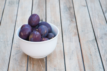 laxative: Arrangement of fresh whole ripe purple damson plums in a bowl and on wooden boards just harvested from the garden and a healthy source of antioxidants Stock Photo