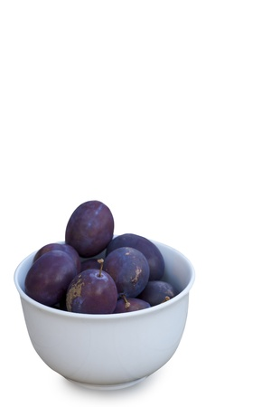 laxative: Ceramic bowl of fresh purple damson plums, a healthy snack rich in antioxidants and eaten dried as prunes for their laxative effect isolated on white with copyspace