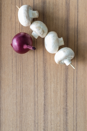 agaricus: Fresh button mushrooms and red onion on a wooden kitchen counter waiting to be used as ingredients in savoury cooking