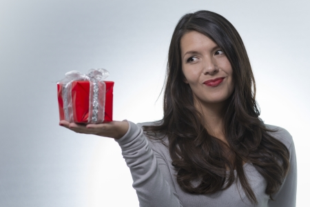 rueful: Woman eyeing a decorative red gift she is showing on the palm of her hand with a rueful smile, studio portrait on grey Stock Photo