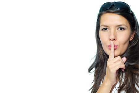 shushing: Woman making a shushing gesture raising her finger to her lips as she requests silence or asks the viewer to share her secret, head and shoulders portrait with copyspace alongside