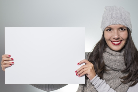 Smiling beautiful young woman in stylish winter fashion holding a blank white sign with copyspace for your text or advertisement photo
