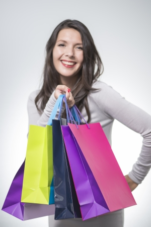 gleeful: Beautiful satisfied woman holding an array of colourful shopping bags smiling happily at her successful spending spree, slective focus