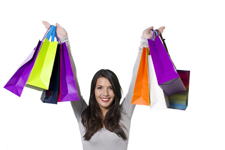 aloft: Jubilant woman shopper holding aloft a collection of colourful shopping bags with a beaming smile rejoicing in all her successful purchases, isolated on white