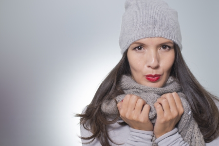 downcast: Pretty young woman in winter fashion cuddling down inside her grey woolly knitted jersey, scarf and cap on a cold day with copyspace Stock Photo