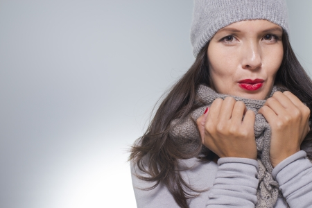 woolly: Pretty young woman in winter fashion cuddling down inside her grey woolly knitted jersey, scarf and cap on a cold day with copyspace Stock Photo
