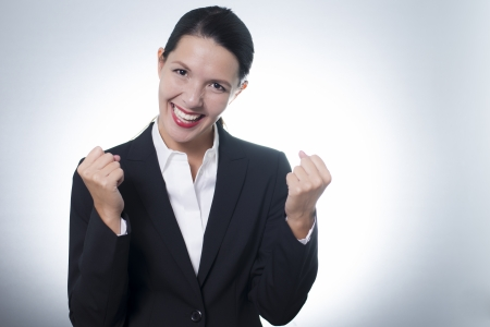 enthusiastic: Beautiful jubilant young businesswoman cheering with a beaming enthusiastic smile on her face as she celebrates a success, with copyspace