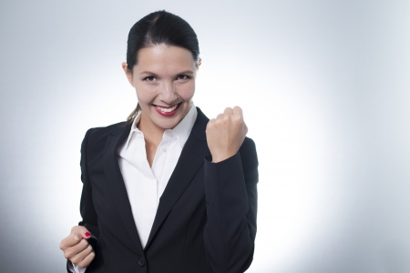jubilation: Beautiful jubilant young businesswoman cheering with a beaming enthusiastic smile on her face as she celebrates a success, with copyspace