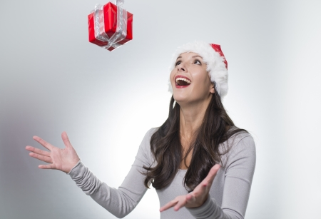 gleeful: Laughing beautiful woman wearing a red Santa hat catching a surprise Christmas gift suspended midair above her outstretched hands with a look of gleeful excitement Stock Photo