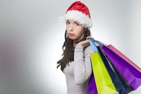 Pretty young woman in a Santa hat standing sulking with a sad face while out Christmas shopping with a handful of colourful shopping bags as she struggles to find suitable gifts for her loved ones photo