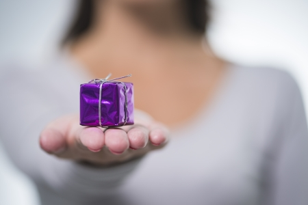 Pretty young woman with long brunette hair holding out a small colourful purple gift for a loved one with selective focus, concept shoot Фото со стока