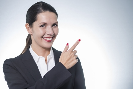 endorsing: Beautiful stylish business woman pointing to copyspace with a beaming friendly smile as she draws your attention to your text or advertisement Stock Photo
