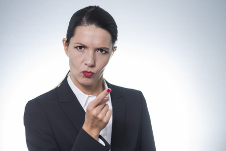 frowns: Stern young business woman or manageress making a finger gesture of displeasure as she frowns at the camera, studio portrait with copyspace