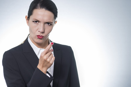 condemnation: Stern young business woman or manageress making a finger gesture of displeasure as she frowns at the camera, studio portrait with copyspace