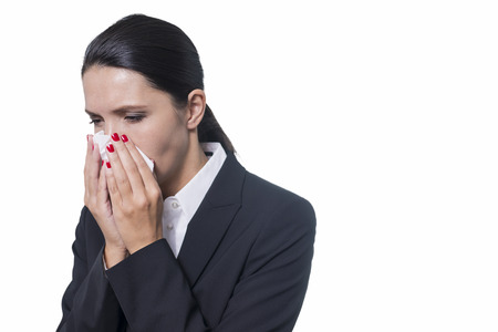 Stylish young businesswoman with a seasonal cold and flu blowing her nose on a handkerchief isolated on white with copyspace photo