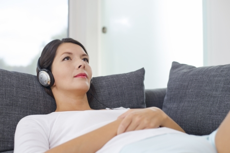 glint: Beautiful serene young woman relaxing with a sensual glint in her eyes listening to music on a set of headphones lying on her back on a sofa in casual shorts