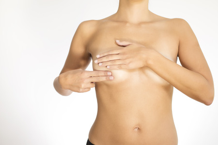 Close up view of the naked torso of a woman testing her breast for cancer flattening the tissue with one hand and manipulating to detect lumps with the fingers on her other hand photo